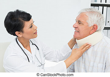 Female doctor examining a senior patients neck - Side view...