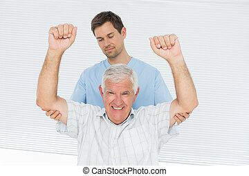 Physiotherapist assisting senior man to raise hands