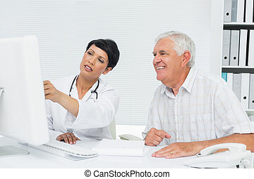 Doctor with male patient reading reports on computer -...