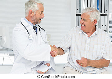 Smiling senior patient and doctor shaking hands in the...
