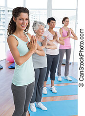 Class standing in namaste pose at yoga class - Happy female...