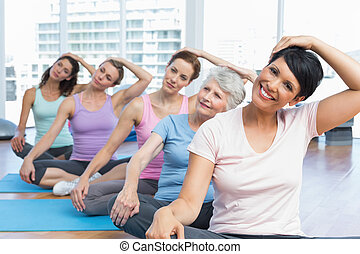 Class stretching neck in row at yog - Female trainer with...