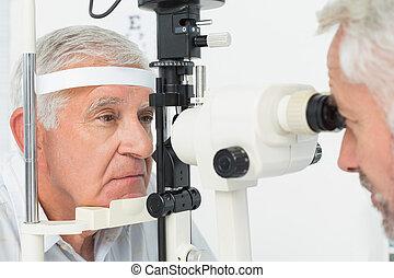 Optometrist doing sight testing for senior patient -...