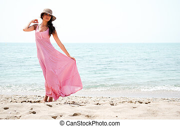 Portrait of a beautiful woman with long pink dress and sun...
