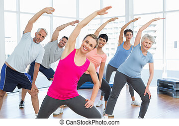 Class stretching hands at yoga class - Happy female trainer...