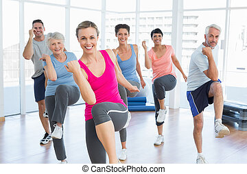 Smiling people doing power fitness exercise at yoga class -...