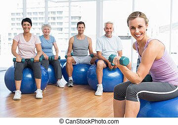 Fitness class with dumbbells sitting on exercise balls -...