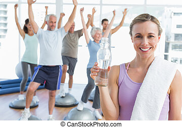 Young woman holding bottle with people stretching hands in the background at fitness studio