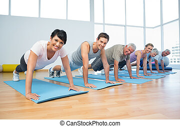 Group doing push ups in row at yoga class - Fitness group...