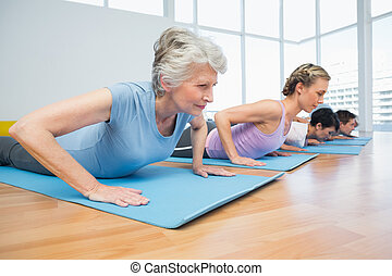Group doing cobra pose in row at yoga class - Fitness group...