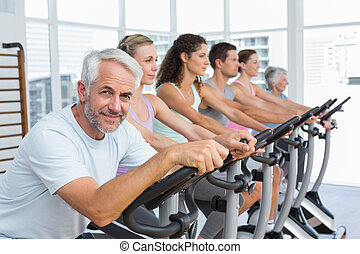People working out at spinning class in gym - Group portrait...