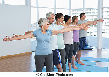 Class stretching hands in row at yoga class - Portrait of...