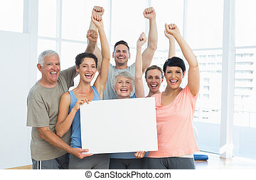 Portrait of happy fit people holding blank board in the yoga...