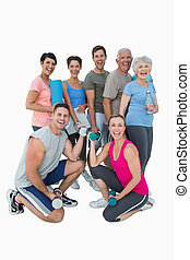 Full length portrait of happy fitness class over white...