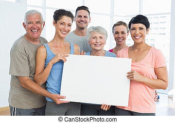 Fit people holding blank board in yoga class - Portrait of...