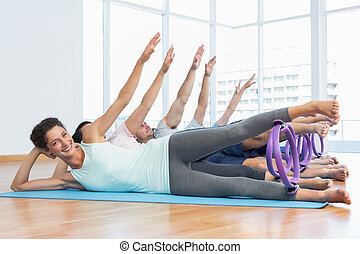 Class stretching legs and hands in row at yoga class - Full...