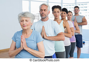 Sporty people with eyes closed and joined hands