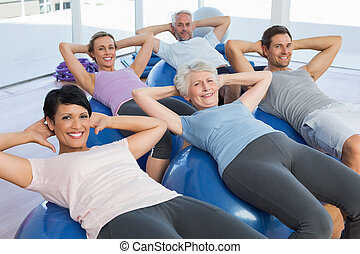 Smiling people stretching on exercise balls - Portrait of...