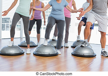 Low section of people doing power fitness exercise at yoga...