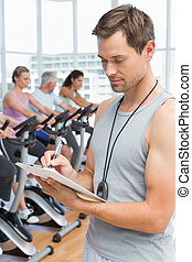 Trainer with people working out at spinning class - Portrait...