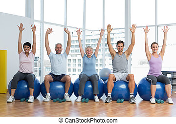 Class sitting on exercise balls and raising hands in gym -...