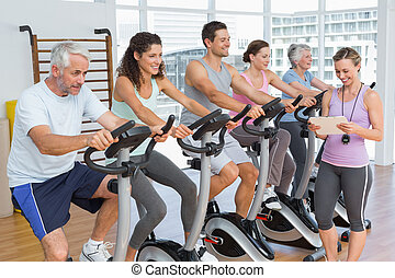 Trainer besides people working out at spinning class -...