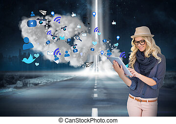 Stylish blonde using tablet pc with app icons and cloud -...