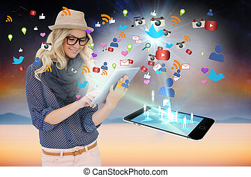 Stylish blonde using tablet pc with app icons and smartphone...