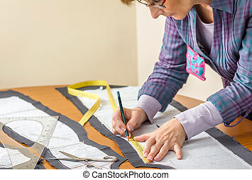 Dressmaker drawing tailor pattern on the table - Woman...