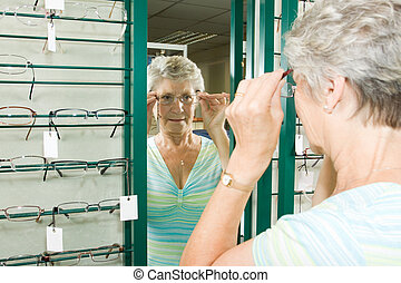 Choosing glasses at the optician - A lady choosing a pair of...
