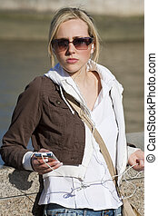 Woman Listening to MP3 Player - A beautiful young blond...