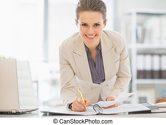 Smiling business woman working in office with documents