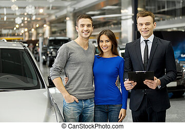 Happy car owners Young couple and handsome car salesman...