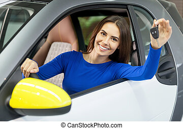 She has bought her dream car! Attractive young woman sitting...