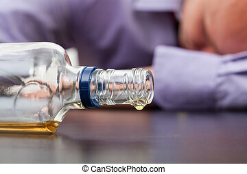 Almost empty bottle of alcohol - Drunk man sleeping with...