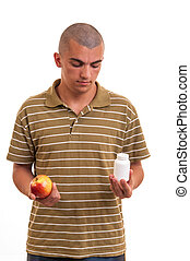 Man offering pill in one hand and apple in another. Copy space boxes with supplements. concept of natural fruit vitamin or pill