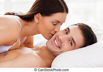 I love her Beautiful young loving couple lying in bed while...