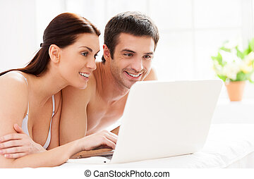 Surfing the net in bed Cheerful young loving couple lying in...