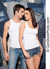 Couple in jeans Beautiful young couple in tank tops and...