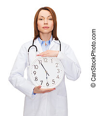 calm female doctor with wall clock - healthcare and medicine...