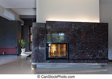 Black stylish fireplace - A black brick wall with a small...