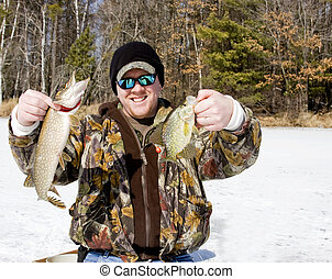 ice fishing catch - ice fisherman holding a northern pike...