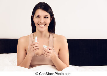Smiling young woman with a bottle of inhalant - Young woman...