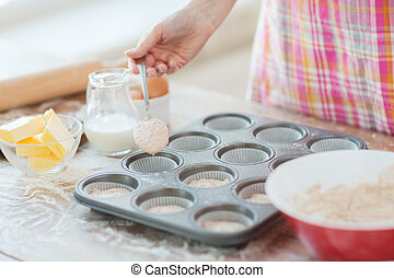 close up of hand filling muffins molds with dough - cooking...