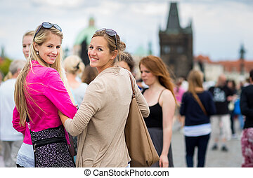 Two pretty, young women sightseeing in Prague historic...