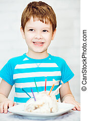 Portrait of a little boy with a cake and candles.