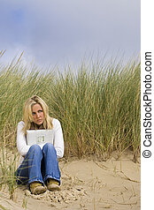 Woman Broken Heartrd At Beach - A young woman sits alone on...