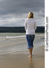 Woman Alone At The Beach - A young woman walks alone on a...