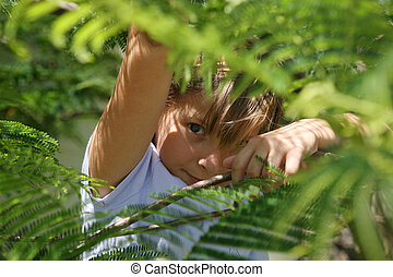 girl hiding under tree