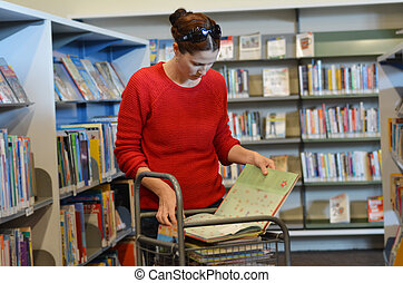 Woman in Library - Young woman selecting book in...